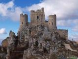 """47- La fortezza di Rocca Calascio (XIII sec.), nel Parco Nazionale del Gran Sasso-Monti della Laga. Il suggestivo castello, posto su una cresta rocciosa a dominio della Piana di Navelli e della vallata del Tirino, è, con i suoi 1.512 m. di altitudine, uno dei fortilizi più elevati d'Europa. Nelle vicinanze della rocca si trova l'antica chiesa di S. Maria della Pietà (XVI sec.). Il castello di Rocca Calascio è stato il set naturale di diversi films di successo, tra cui """"Lady Hawke"""", """"Il nome della rosa"""" e """"Padre Pio"""". ,"""