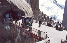 """44 - Il ponte che collega il Piton Central al Piton Nord. Si vede chiaramente l'imbocco della """"Galleria del Monte Bianco"""" e della """"Galleria della Vallée Blanche"""", che portano rispettivamente alla partenza della cabinovia per la Punta Helbronner e all'ascensore per la terrazza della cima del Piton Central."""