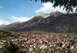79 - Panorama di Aosta sullo sfondo il Monte Emilius-- Di grande interesse la Cattedrale di Santa Maria Assunta, con la visita agli scavi archeologici posti sotto l'attuale pavimento, la caratteristica Piazza Chanoux ed il complesso monumentale della Collegiata di Sant'Orso risalente all'XI sec. Proprio a Sant'Orso è intitolata la fiera che si ripete ogni anno ad Aosta alla fine di gennaio. Migliaia di turisti riempiono le vie del centro città, che si vestono a festa, esibendo la più antica produzione artigiana valdostana, dalla scultura al legno, dal ferro battuto alla pietra ollare, cuoio, vimini, stoffe in lana, merletti, giochi e maschere.