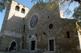 13- Trieste La Cattedrale, è il risultato dell'unione della Chiesa di Santa Maria e di quella dedicata a San Giusto avvenuta negli anni tra il 1302 e il 1320. La facciata è semplice, impreziosita da un grande rosone gotico e da un portale centrale con elementi di una stele funeraria romana. La lapide sopra la porta ricorda il bombardamento austro-inglese del 1813 contro le truppe napoleoniche che si nascondevano nel vicino Castello. Alcune palle di cannone sono visibili nel muro del campanile, che ingloba anche i resti del propileo di un tempio romano e un'edicola con la statua di S. Giusto.