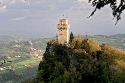 """22 - San Marino - Infine, la Terza Torre detta del Montale risale a fine XIII° secolo. E' la più """"piccola"""" per dimensioni, ma per la difesa, ha ricoperto un ruolo strategico: è collocata infatti nella migliore posizione per la vedetta. Si tratta di un fortilizio dalla pianta pentagonale, restaurato diverse volte nel corso dei secoli, l'ultima nel 1935. L'interno contiene una prigione profonda 8 metri detta """"fondo della torre"""". Intorno al Montale si vedono grossi massi di roccia molto antichi, sovrapposti in modo primitivo a guisa di muri. Il tratto di mura che dalla Seconda Torre porta al parcheggio della cava antica, appartiene ai resti della seconda cinta di mura della città costruita nel XIII secolo. La città di San Marino, infatti, era fortificata da tre cinta di mura costruite in tre differenti epoche e in gran parte abbattute per permettere l'espandersi della città."""