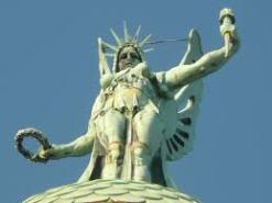 """57 - Trieste. La statua della vittoria alata sulla cima del faro In alto c'è la Vittoria Alata, statua di sette metri che impugna una corona d'alloro nella mano destra e una fiaccola nella sinistra. Per proteggerla dal forte vento di Bora, è stata progettata con un complesso meccanismo interno che fa """"sbattere"""" (impercettibilmente) le ali in modo da assorbire le raffiche di vento. Sotto la statua c'è il faro, ancora oggi il più potente dell'Adriatico."""