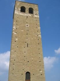 13 - San Leo. Torre civica campanaria. E' il monumento più appartato di San Leo, non per sua mole, massiccia e imponente, quanto per sua collocazione impervia ed una sorta d'innata alterigia che, ancor'oggi, intimorisce ed allontana. Il campanile-torre è edificio di grande bellezza, opera compiuta del romanico anzi, emblematico esempio di quello stile architettonico. L'architettura come escrescenza naturale della roccia su cui è fondata, un tutt'uno con la stessa roccia, come da parabola evangelica: manifesto della fede cristiana per secoli. Storicamente sappiamo ben poco della torre, che nell' impianto esterno è certamente contemporanea all'adiacente cattedrale del 1173. Il suo perimetro quadrato ingloba ed occulta all'interno una costruzione a piante circolare, alta sino alla cella campanaria.