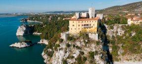 """67 - Trieste. Il castello di Duino - Arroccato su uno sperone carsico a picco sul mare, con un panorama mozzafiato su tutto il golfo di Trieste, il castello di Duino è un'affascinante meta turistica: la sua bellezza è accresciuta anche da quell'atmosfera calda e gioiosa che la presenza dei proprietari, i componenti la nobile famiglia dei principi della Torre e Tasso (Thurn und Taxis), conferisce alla storica dimora, rendendola viva, lontana dalla fredda austerità """"museale""""."""