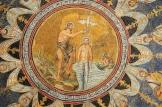 79 - Il Battesimo di Gesù è un particolare del ciclo di mosaici che rivestono l'interno della cupola del Battistero Neoniano (Battistero degli Ortodossi). Egli appare immerso fino alla vita nelle acque trasparenti del fiume Giordano. Il Battista, in piedi alla sua destra, sulla riva rocciosa del fiume, regge con la mano sinistra una croce gemmata mentre con la mano destra versa l'acqua sul capo del Redentore. Perpendicolarmente al capo di Gesù scende una colomba con le ali spiegate che simboleggia lo Spirito Santo. A sinistra del Cristo avanza, immerso fino al busto, un vecchio di proporzioni più piccole rispetto alle altre figure quale personificazione simbolica del fiume Giordano, che reca tra le mani un panno verde allo scopo di asciugare il Redentore all'uscita dalle acque.
