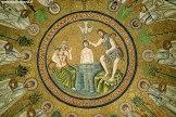 80 - Mosaici a Confronto - Il mosaico della cupola del Battistero Neoniano può essere confrontato con questo mosaico della cupola del Battistero degli Ariani risalente all'epoca di Teodorico (493-526 d.C). In quest'ultimo il battesimo di Gesù è sempre collocato al centro della cupola all'interno di un medaglione circolare ma, a differenza di quello Neoniano, la figura di Gesù viene posta al centro della composizione e Giovanni alla sua sinistra appare seduto sulle rocce con il braccio posto sulla testa di Cristo, come vuole l'usanza bizantina e l'altro che regge un bastone, simbolo del deserto. Alla destra di Gesù il vecchio, anch'esso seduto, cinto da una veste tiene in mano una canna palustre e ha sul capo delle chele di granchio, come fosse una divinità marina. Lo sfondo anche in questo caso è risolto con le tessere dorate.