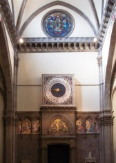 """49 - Firenze. Controfaccia interno Duomo. Al centro della controfacciata l'orologio italico ha teste di evangelisti. dipinte agli angoli da Paolo Uccello (1443). L'orologio, di uso liturgico, è uno degli ultimi funzionanti che usa la cosiddetta hora italica, un giorno diviso in 24 """"ore"""" di durata variabile a seconda delle stagioni, che comincia al suono dei vespri, in uso fino al XVIII secolo. I ritratti degli evangelisti non sono identificabili col tradizionale ausilio degli animali-simbolo, ma attraverso i tratti fisionomici che richiamano l'animale (o, nel caso di Matteo, l'angelo) simbolico.Nella lunetta del portale centrale si trova il mosaico dell' Inocornazione della Vergine, attribuito a Gaddo Gaddi. Ai lati del portale angeli in stile arcaizzante forse dipinti da Santi di Tito alla fine del Cinquecento. A destra del portale centrale si trova poi la tomba del vescovo Antonio d'Orso (1343) di Tino di Camaino. Il pilastro attiguo ha una tavola a fondo oro con Santa Caterina d'Alessandria e un devoto riferibile alla scuola di Bernardo Daddi (1340 circa)[9]."""