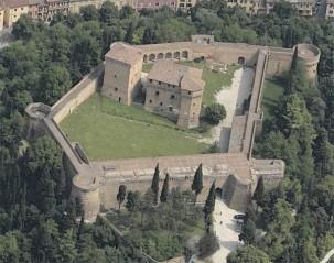 67 - Cesena - Rocca Malataestiana. Veduta aerea. La Rocca Malatestiana, posta sulla sommità del Colle Garampo e circondata dal Parco della Rimembranza, è una fortezza nata per difendere la città di Cesena; l'attuale è la terza fortificazione costruita a poca distanza dalle rovine delle due precedenti di epoca tardo-romana e medievale. Iniziata da Galeotto Malatesta a partire dal 1380, la Rocca venne proseguita dai suoi successori Andrea e Malatesta Novello e ultimata durante il dominio pontificio, intorno al 1480. Il perimetro a pianta pentagonale, percorso da camminamenti interni, presenta due ingressi ed è costituito da possenti cortine intervallate da tre torrioni poligonali alternati a tre circolari; quello circolare di levante fu realizzato sotto la direzione dell'architetto Matteo Nuti.All'interno della cinta due imponenti architetture, il maschio e la femmina, costituiscono la cittadella fortificata.
