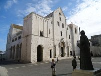 12 - Bari -Basilica o Duomo di San Nicola - La costruzione della grande basilica fu determinata dall'arrivo a Bari delle reliquie di San Nicola, vescovo di Mira (Turchia), portate da mercanti baresi. L' esterno, in pietra calcarea, è semplicissimo. L' interno, di tipo basilicale, fu in parte alterato nel Seicento. Di grande importanza è l'arredo originario della basilica, in particolare si segnalano il pavimento, la cattedra episcopale ed il ciborio, tutte opere del XII secolo. La cripta, sostenuta da colonne dotate di notevoli capitelli romanici e bizantini, contiene la tomba del santo. Molto prezioso è il Tesoro della basilica, conservato nel Museo omonimo allestito all' interno della chiesa stessa.