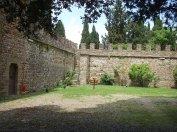 176 -Fiesole -Il Castel di Poggio, Il cortile è mantenuto a prato ed è ombreggiato da sparsi pini e cipressi. Il grande bosco attorno al castello che fa parte della proprietà è composto da lecci, castagni, querce e cipressi, punteggiato da statue e con alcuni uliveti tenuti a prato.