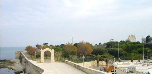 54 - Trani. La villa comunale di Trani è, senza dubbio, uno dei più affascinanti giardini sul mare della Puglia. Si trova accanto alle vecchie mura; è piena di lecci, pini marittimi, aiuole, palme e fontane. Si affaccia sul mare, proiettata lontano, con uno sguardo ampio che va dalla Cattedrale alla penisola di Colonna.