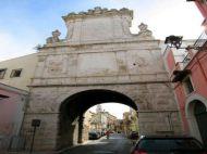 """9 - Andria. La porta di Sant'Andrea è l'unica porta conservata e che si erge a ricordo dell'unione tra Federico II di Svevia e la città di Andria. Costruita nel 1593. la Porta è nota anche come """"arco di Federico"""". Sotto l'iscrizione è incisa la data """"1230"""" che ricorda come solo la città di Andria si dimostrò fedele all'imperatore Federico II quando giunse in Puglia."""