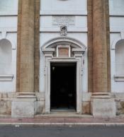 156 -Taranto. Chiesa del Carmine, portale di ingresso inquadrato da quattro nicchie laterali e una finestra. L'impianto della chiesa è a croce latina con unica navata affiancata da cappelle su entrambi i lati che ospitano statue realizzate da maestri cartapestai leccesi. circolare in asse con l'ingresso.