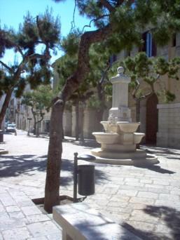 38 -Fasano. Esternamente, si può vedere una parte della struttura del monastero. I Portici delle Teresiane con la fontana.