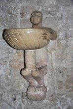 17 -Duomo_interno. Risalente al XII secolo, l'acquasantiera, detta del saraceno, posta a destra dell'ingresso meridionale, ci mostra un uomo dai tratti africani che regge la vasca dell'acqua.