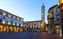 """39 -Viterbo. Al centro si trova il Palazzo dei Priori, che ospita il Municipio. Un corridoio che sovrasta via Ascenzi che, mette in comunicazione il Palazzo dei Priori con il Palazzo del Podestà. Dalla parte opposta del Palazzo del Podestà c'è il Palazzo del Capitano del Popolo, oggi sede della Prefettura.All'inizio di Via Roma, all'angolo del palazzo del Podestà c'è un leone, simbolo della città, scolpito in una pietra chiamata """"nenfro""""."""