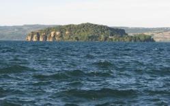 10 - Sul lago di Bolsena. L'isola Martana, posta di fronte all'abitato di Marta, da cui dista circa 2 Km, ha la forma di mezzaluna che rappresenta la metà emergente di un cratere vulcanico in parte sprofondato nel lago. Il versante Nord si presenta come una ripida parete a strapiombo sull'acqua, mentre il lato Sud, meno scosceso, è fertile e ricoperto da lecci ed ulivi. Il convento dell'isola ha ospitato vari ordini di monaci: i Benedettini, gli Agostiniani e i Paolotti, ma già nel 1459, era ormai deserto. Diventata proprietà privata a metà del XX secolo, l'isola appartiene ora ad una società che l'ha fornita di luce elettrica e ne gestisce la manutenzione. Lo sbarco sull'isola è consentito unicamente su permesso di tale società.