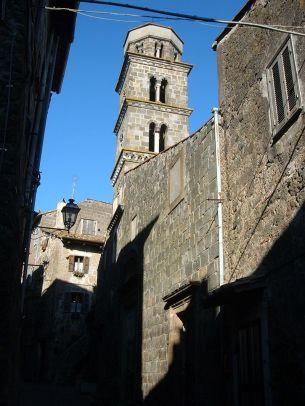 23 --Ronciglione, la struttura esterna e il campanile fatto erigere dal Conte Everso degli Anguillara nel 1436 per mano del maestro Galasto. È composto da piani con finestre in successione monofore, bifore e trifore e da un ultimo piano a pianta ottagonale, sulla porzione di facciata della Chiesa ancora presente, composta da pietre a vista, è visibile lo stemma degli Anguillara.