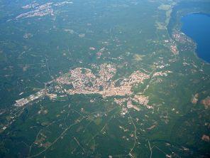 12 -Vista aerea di Ronciglione, 3,7 km da Caprarola A destra il lago di Vico.Posizionata sulle alture meridionali dei Monti Cimini, la parte medioevale di Ronciglione sorge su un grosso ciglione tufaceo, posto alla confluenza di due corsi d'acqua, il Rio Vicano, emissario del Lago di Vico, e il Fosso Chianello che, dopo le colmate farnesiane del XVI secolo, ora scorre sotterraneo.