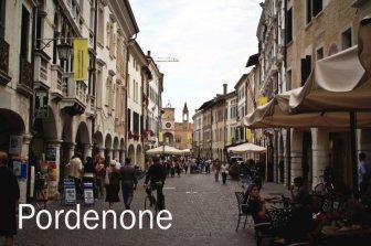 """12 -Corso Vittorio Emanuele II, via principale della città vecchia, affiancato da palazzi porticati gotici e rinascimentali con affreschi, esempio mirabile di porticato veneto e da alcuni chiamato piccolo """"Canal Grande senz'acqua. Sullo sfondo il Palazzo comunale."""