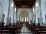 13 -Cattedrale di San Marco a Latina. Nella parete fondale della navata centrale, si apre la profonda abside, affiancata a sinistra dal tabernacolo e, a destra, dalla statua raffigurante San Marco Evangelista di F. Magni. L'abside ospita il presbiterio, rialzato di alcuni gradini rispetto al resto della chiesa, al centro del quale si trova l'altare maggiore, sovrastato dal Crocifisso, alle spalle del quale vi è la cattedra episcopale. La parete fondale è decorata da una fascia di moderni mosaici, opera di V. Cinti.