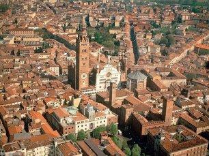 """1 -Cremona. Panorama della città che si trova nel cuore della Pianura Padana, poco distante dalle rive del fiume Po. È nota come la """"città delle tre T"""", turòon, Turàs, tetàs (torrone, Torrazzo, tettone). Altra versione è """"turòon, Turàs, Tugnàs"""", """"torrone, Torrazzo, Tognazzi"""" (vi è nato Ugo Tognazzi)."""