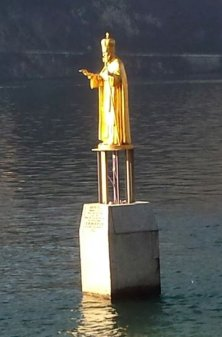 9 -Lecco. Monumento a San Nicolò,. questa statua è posizionata su un basamento tra le acque del lago a Punta della Maddalena, nei pressi della foce del torrente Gerenzone uno dei tre torrenti che attraversano la città di Lecco, posizionata nel 1955 e restaurata nel 2013, l'opera in bronzo ricoperta da foglie d'oro alta due metri di Giacomo Luzzana, raffigura il santo in parametri vescovili orientali nel gesto di proteggere il lago e la città