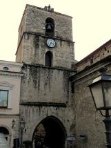8 -Isernia. Cattedrale, Il campanile della chiesa, situato tra il fianco sinistro del tempio e l'Università, fu realizzato nel 1349 ed è attraversato dal cosiddetto Arco di San Pietro. I due ingressi dell'arco sono sorvegliati da quattro statue togate romane.