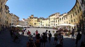 """4 -Lucca. Piazza. Anfiteatro. L'armonia di questa piazza si coglie ammirandola dal centro ed è dovuta in gran parte all'assenza di grandi aperture. L'accesso alla piazza, infatti, avviene da quattro piccole porte a volta e questo le dà l'aspetto di """"piazza chiusa"""". Il punto di intersezione tra le 4 porte è indicato da una mattonella in ceramica al centro della piazza. I negozi, i locali, i tavolini all'aperto dei bar e il mercato settimanale ne fanno il cuore di Lucca, punto obbligato di passaggio e sosta di cittadini e turisti."""
