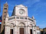 9 -Grosseto, il Duomo, cattedrale di San Lorenzo patrono della città, è il luogo di culto cattolico più importante. La costruzione ha inizio 1300 e il campanile fu annesso nel 1400 circa. La facciata ottocentesca ha un grande rosone centrale dove vi sono i simboli dei quattro evangelisti.