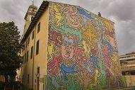 """38 -Pisa. Il Murales di Keith Haring. Nel 1989 di passaggio a Pisa, Keith Haring lascia alla città una straordinaria opera d'arte: è il murales """"Tuttomondo"""", dipinto sulla facciata posteriore del convento dei frati """"Servi di Maria"""" della chiesa di S. Antonio che si trova a pochi metri dalla stazione. Questo è stato uno dei suoi ultimi murales. Dopo 20 anni """"Tuttomondo"""" è ancora lì a ricordarci la vita breve e intensissima di questo straordinario artista."""